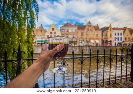 Full glass of beer on Brugge cityscape background. Hand with beer glass in Bruges, Belgium.