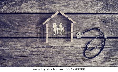 Cut outs of a family with kids in a house with a stethoscope lying on a wooden table alongside in a conceptual image.