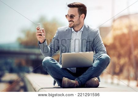 Attractive man sitting outside,using mobile phone and laptop-looking down while sitting with legs crossed.