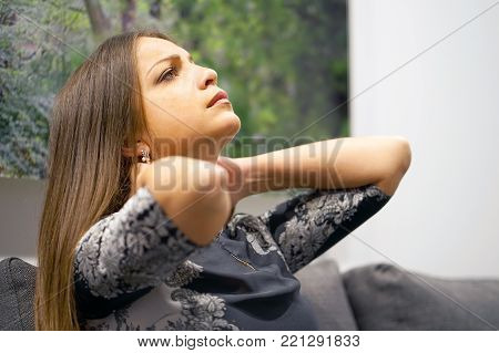 Tired neck. Beautiful young woman suffering from neck pain at home on couch. Brunette, a woman's sense of fatigue, exhausted, stressed. A girl massages her painful neck with her hands. The concept of body and health.