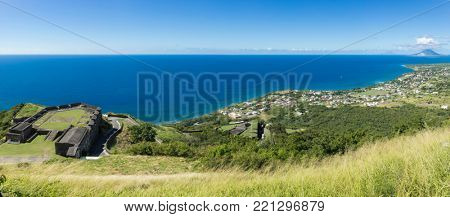Panorama of St Kitts, including Brimstone Fortress and the shore of the Caribbean Sea.