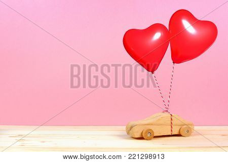 Wooden Toy Car With Red Heart Balloons Against A Pink Background. Valentines Day Or Love Concept.