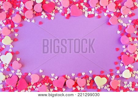 Frame of assorted Valentines Day sweets and candy over a pastel purple background