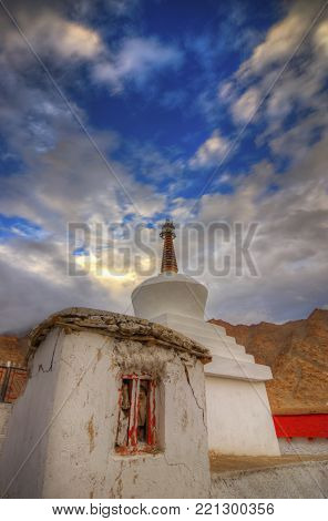 Buddhist Stupa at Likir Monastery with blue sky and rising Sun in the background, Ladakh, India