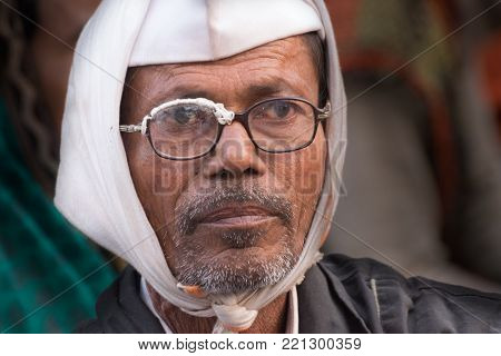 BABUGHAT, KOLKATA, WEST BENGAL / INDIA - 11TH JANUARY 2015 : Aged Indian man with borken spectacles loking out , at Gangasagar transit camp.
