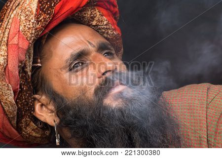 BABUGHAT, KOLKATA, WEST BENGAL / INDIA - 11TH JANUARY 2015 : Indian Hindu Sadhu smoking marijuana, locally called Ganja, a form of canabis sativa . On his way to Gangasagar, India.