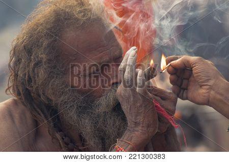 BABUGHAT, KOLKATA, WEST BENGAL / INDIA - 11TH JANUARY 2015 : Hindu Sadhu smoking marijuana, locally called Ganja, a form of canabis sativa .