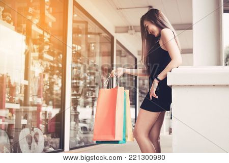 Asian young woman shopping in the outlet mall with carrying paper bags.