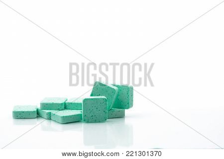 Macro shot to show detail of green medical lozenges for relief cough, sore throat and throat irritation on white background with copy space. Apple flavored.