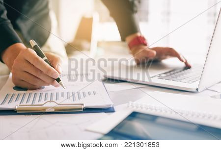 Business People Examining Financial Reports And Analyzing Business Growth In Tablet Screen.