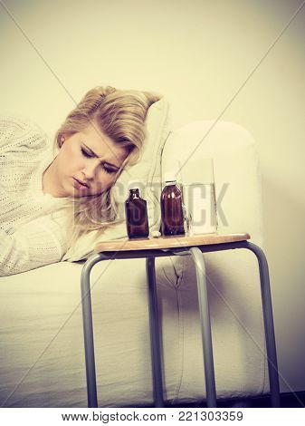 Sad sick woman lying on couch having horrible flu, table with medicines and pills standing next to her.