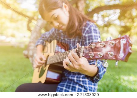 Female fingers playing guitar outdoor in summer park. Musician woman and her guitar in nature park, Practice guitar.
