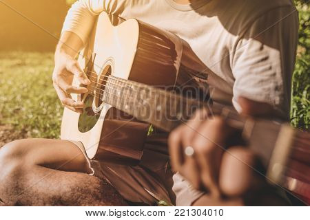 Man fingers playing guitar outdoor in summer park. Musician man and her guitar in nature park, Practice guitar. vintage tone.