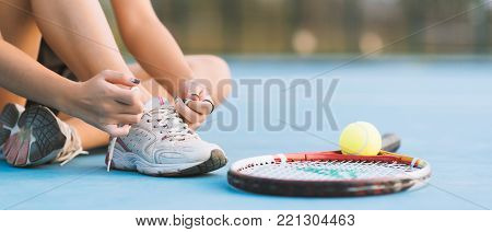 Tennis player tying shoelaces in court. vintage tone banner panoramic crop for copy space. tennis on sunset. tennis sport girl. tennis racket. tennis player