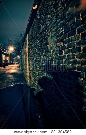 Scary shadow on a vintage brick wall in a dark, gritty and wet Chicago alley at night after rain.