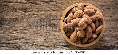 Almonds in brown bowl on textured wooden background, top view. banner panoramic crop for copy space. Close up almond background.  almonds for texture.