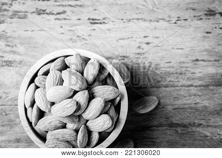 Almonds in brown bowl on textured wooden background, top view. Close up almond background.  almonds for texture.
