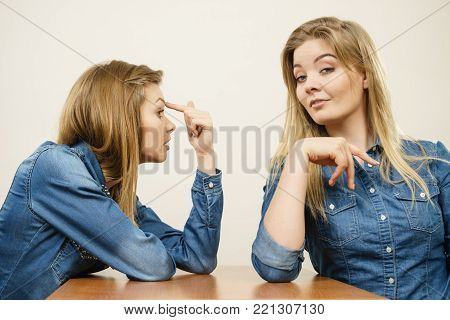 Woman saying bad things about her over confient female friend. Pointing at forehead, stupidity gesture.