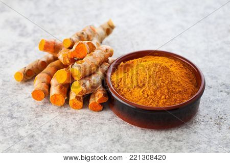 Turmeric powder and fresh turmeric on wooden background - herbs and spices