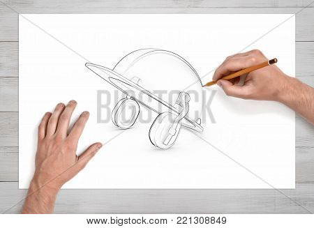 Two male hands draw a pencil sketch of an industrial hard hat with earmuffs on white paper. Industrial equipment design. Protective gear. Manual work.