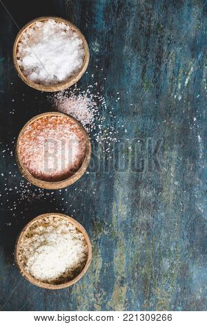 Different types of natural salt in coconut shell bowls on wooden surface. Pink Himalayan Salt, Grey Sea Salt and White Sea Salt