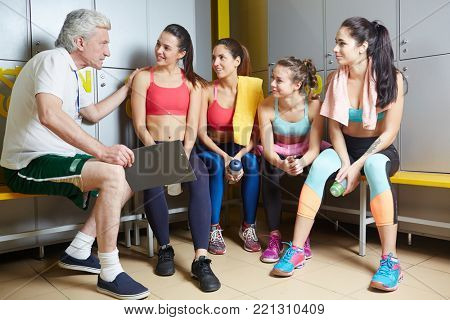 Aged trainee encouraging his team of young females before competition