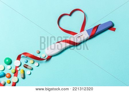 Treatment of infertility with pills, help in conceiving a child. Tablets from pregnancy do not work, contraception. Positive pregnancy test with two strips and a red ribbon in the form of a heart