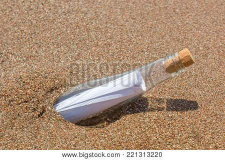 Paper Message in a glass bottle with a cork on the sand. A note on salvation, please help