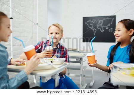 Happy classmates with drinks having talk at lunch-break in classroom