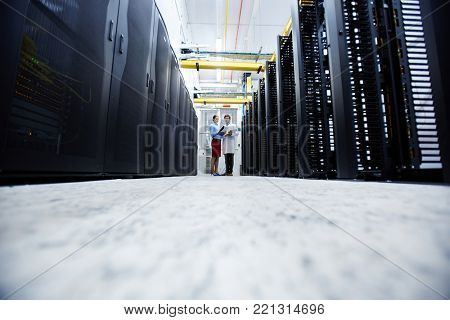 Young mining farm staff standing at the end of long aisle and having talk