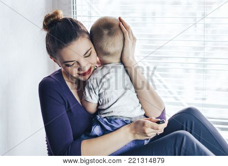 Young mother holding her baby boy in her lap, playing and enjoying motherhood. Hugging her baby. Focus on the baby. Sitting on windowsill, near window.