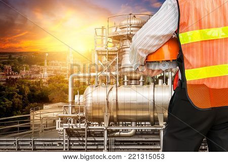 Engineer man in safety uniform at the oil industrial refiner on sunset background