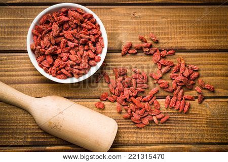 Dried goji berries on wooden table. Top view.