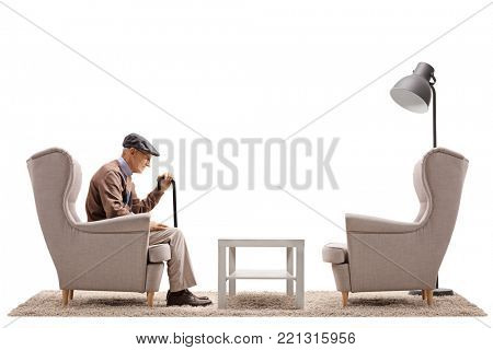 Lonely senior sitting in an armchair isolated on white background