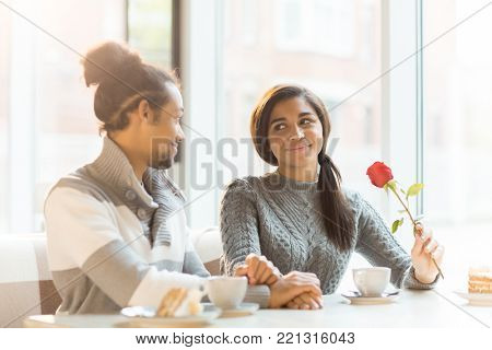 Young amorous man and woman holding by hands and looking at one another during date in cafe