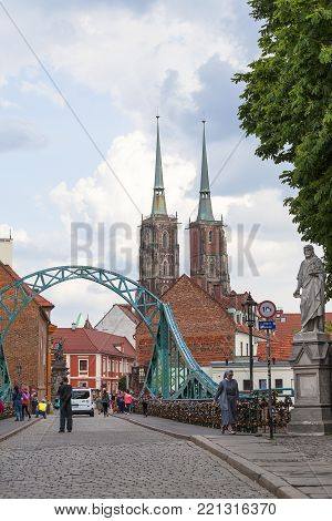 WROCLAW - POLAND, JUNE 12, 2017: Wroclaw Cathedral (Cathedral of St. John the Baptist), gothic style 13th century church and Tumski Bridge on Ostrow Tumski Island. It is the oldest part of the city of Wroclaw