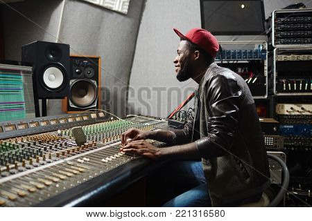 Happy young rapper sitting by recording equipment in audio production studio