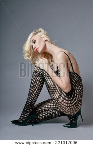 Nude Sexy Blond Woman In Lingerie Bodysuit With A Perfect Body Sitting On The Floor. Fetish Lingerie
