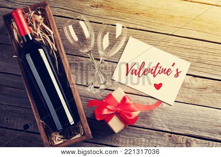 Valentines day greeting card. Red wine and gift box on wooden table. Top view with copy space