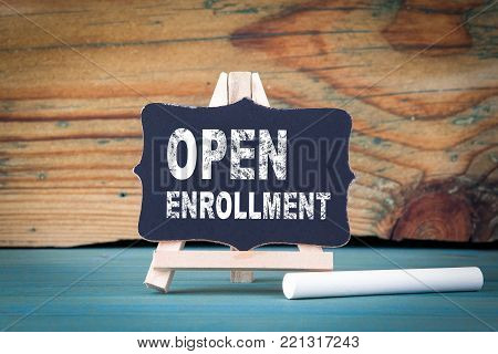 Open Enrollment. small wooden board with chalk on the table.
