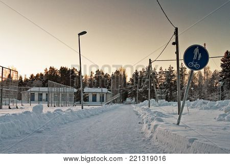 A snowy footpath leads to the rural town of Oulainen in the Northern Finland. The frost has covered just about everything by the path.