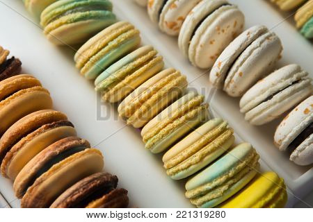 Set of different french cookies macaroons in a white box. Closeup. Coffee, chocolate, vanilla, lemon, raspberry, strawberry, pistachio, violet, rose, orange tastes macaroons.