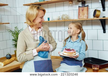 Little girl holding yummy homemade dessert and looking at her grandmother in the kitchen