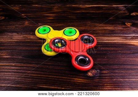 Yellow and red fidget spinners on rustic wooden desk