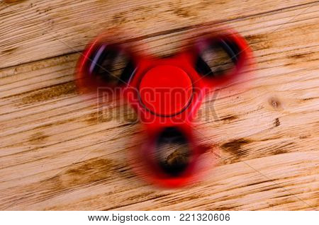 Red fidget spinner rotates on rustic wooden desk