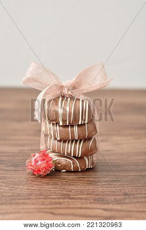 A stack of chocolate covered biscuits tied with a pink ribbon and an artificial rose