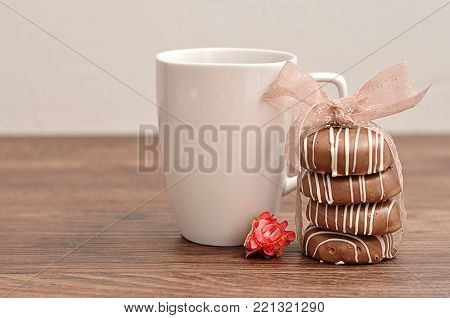 A stack of chocolate covered biscuits tied with a pink ribbon, an artificial rose and a  white mug