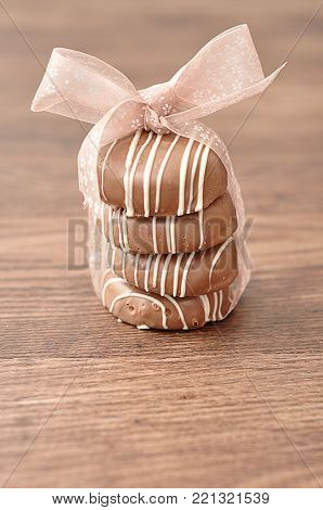 A stack of chocolate covered biscuits tied with a pink bow