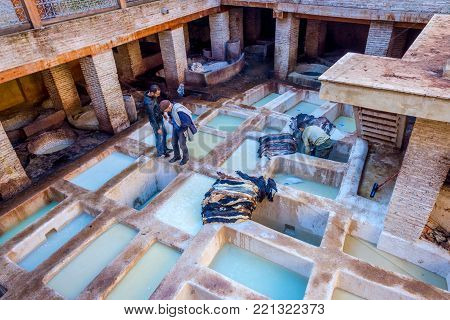 FEZ, MOROCCO - DECEMBER 10: Man putting the skins to dry at one of the tanneries in Fez old town. December 2016