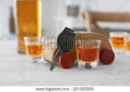 Composition with alcohol, toy and car key on wooden table. Don't drink and drive concept